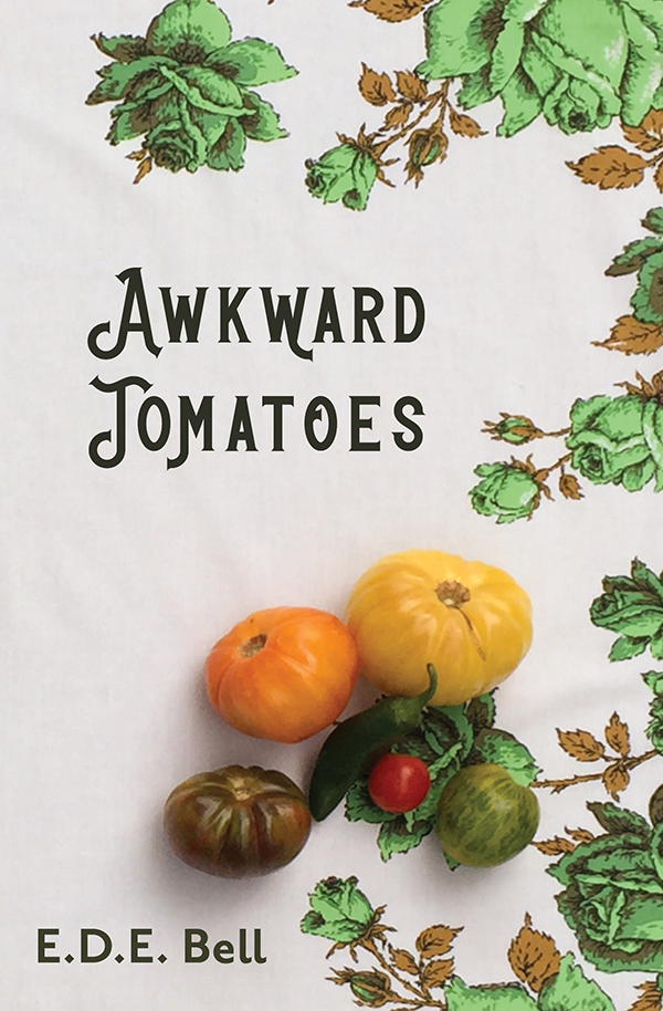 Awkward Tomatoes Cover: Colorful heirloom tomatoes sit on the bottom half of the image on a white vintage tablecloth with a green rose pattern. The title is spelled out in a vintage font on the upper half, and the bottom displays the author name.