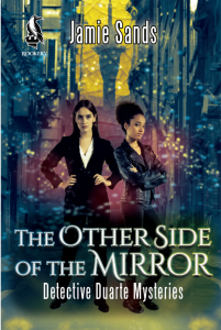 """Two people stand together in front of a cityscape, the Auckland Sky Tower is centred. The woman on the left is caucasian with long dark hair and a serious expression, wearing a pant suit. The person on the left has brown skin, curly hair up in a ponytail and wears a leather jacket. The title reads """"The Other Side of the Mirror: Detective Duarte Mysteries by Jamie Sands"""""""